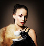 Portrait of a young woman in fur holding a cup of coffee Stock Images