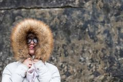 Portrait of a young woman in a fur jacket. Against a wall grunge background Stock Photo