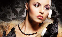 Portrait of a young woman in fur talking on the phone Royalty Free Stock Photography