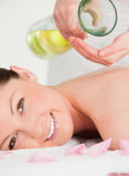 Portrait of a young woman getting massage oil. On her back in a spa stock photos