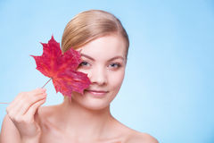 Portrait of young woman girl with red maple leaf. Royalty Free Stock Photo
