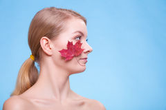 Portrait of young woman girl with red maple leaf. Stock Photo