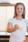 Portrait of a young woman giving a glass of milk Stock Images