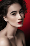 Makeup model. Portrait of young glamorous makeup woman model with thoughtful expression, part red background Royalty Free Stock Photography