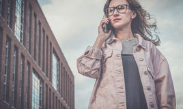 Portrait of young woman in glasses standing outdoors and talking on cellphone.Girl is walking along city street Stock Photo