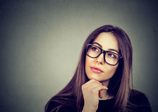 Portrait of a young woman in glasses thinking Royalty Free Stock Images