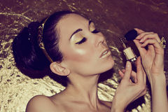 Portrait of young woman with gold makeup Stock Photos