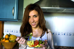 Portrait of young woman with green eyes eating salad Royalty Free Stock Images