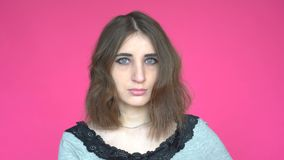 Portrait of young woman with green eyes looking at camera on pink background` stock video
