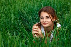 Portrait of a young woman in green grass stock photography