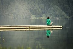 Portrait of young woman in green sweatshirt. Portrait of young woman in green sweatshirt sitting on the edge of pier and meditating. There is volcanic lake on royalty free stock photo