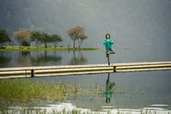 Portrait of young woman in green sweatshirt. Portrait of young woman in green sweatshirt standing on the edge of pier and meditating. There is volcanic lake on royalty free stock photography