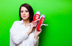 Portrait of young woman with gumshoes. Portrait of the beautiful young woman with red gumshoes on the green background Royalty Free Stock Photography