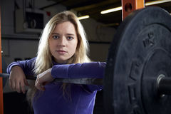 Portrait Of Young Woman In Gym Lifting Weights On Barbell Stock Images