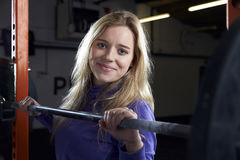 Portrait Of Young Woman In Gym Lifting Weights On Barbell Stock Image