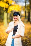 Portrait of young smiling woman with hair, dressed in coat near branches of a tree with yellow foliage for a walk in the park. Por. Portrait of young woman with Stock Image