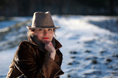Portrait of a young woman with hat. Beautiful young woman in a park in winter time royalty free stock photos