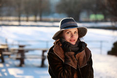 Portrait of a young woman with hat. Beautiful young woman in a park in winter time royalty free stock image