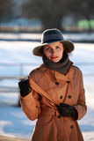 Portrait of a young woman with hat. Beautiful young woman in a park in winter time stock image