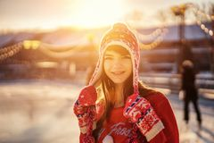 Portrait of a young woman in a hat on the ice rink, a smile on his face, the sun royalty free stock images