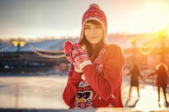 Portrait of a young woman in a hat on the ice rink, a smile on his face, the sun stock image