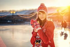 Portrait of a young woman in a hat on the ice rink, a smile on his face, the sun royalty free stock photography
