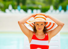 Portrait of young woman in hat sitting on sunbed Stock Images