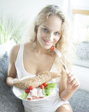 Portrait of young woman having breakfast while sitting on sofa at home Royalty Free Stock Photography