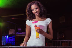 Portrait of young woman having a cocktail at bar counter Royalty Free Stock Images