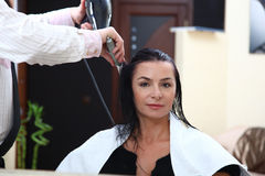 Portrait of young woman having her hair being cut Royalty Free Stock Photos