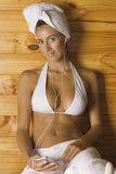 Portrait of a young woman having sauna and listening to an MP3 player Royalty Free Stock Images