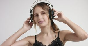 Portrait of a young woman in headphones. Blond young woman in headphones and black lacy camisole listening to music in headphones and dancing stock video footage