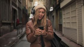 Portrait of young woman teenager with headphones listening to music on phone, sing and funny dancing in street on old stock footage