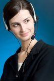 Portrait of young woman with headset, on blue background, smiling. Closeup portrait of young woman with headset, on blue background, smiling Royalty Free Stock Images