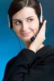 Portrait of young woman with headset, on blue background, smiling. Closeup portrait of young woman with headset, on blue background, smiling Stock Photo