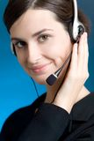 Portrait of young woman with headset, on blue background, smiling Stock Photos
