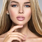 Young Woman with healthy skin of a face. Portrait of  Young Woman with healthy skin of a face. Attractive female with long light straight  hairs and brown make Stock Photos