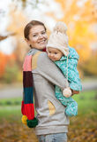 Portrait of young woman and her baby son in park Stock Photos