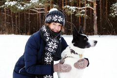Portrait of young woman with her black and white dog on a background of winter coniferous forest. royalty free stock photo
