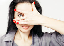 Portrait of young woman with only her eye visable through her hands. Brunett girl peeking through fingers Stock Photography