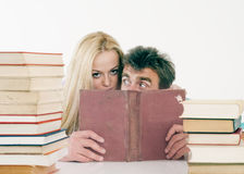 Portrait of a young woman and her teacher. Portrait of a young women and her teacher hiding behind the books Royalty Free Stock Images