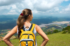 Portrait young woman hiker with backpack standing on top of the Royalty Free Stock Images