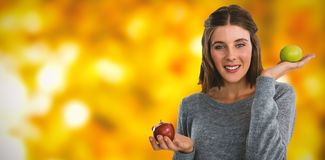 Composite image of portrait of young woman holding apples. Portrait of young woman holding apples against defocused leaves stock image