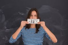 Woman holding a banknote in front of chalk drawing board Royalty Free Stock Images