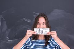 Woman holding a banknote in front of chalk drawing board Royalty Free Stock Image