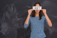 Woman holding a banknote in front of chalk drawing board. Portrait of a young woman holding a banknote in front of chalk drawing board Royalty Free Stock Images