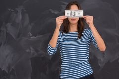 Woman holding a banknote in front of chalk drawing board Stock Image