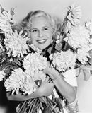 Portrait of a young woman holding a bunch of flowers looking happy Stock Image