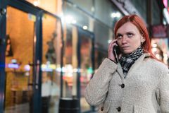 Portrait of young woman holding cellphone in hands on the street in summer, looking at irritated expression, anger, irritation, royalty free stock photos