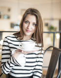 Portrait of young woman holding coffee cup and saucer at cafe Royalty Free Stock Image